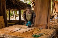 De Afrikaanse mens die zijn werk doet maakt een beeldhouwerdeur stock foto
