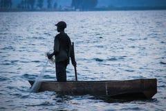 De Afrikaanse visser in een boot verminderde de vissen netto in het water bij schemer stock fotografie