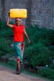 De Afrikaanse vrouw draagt dingen op haar hoofd Stock Foto's
