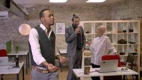 De Afrikaanse zakenman danst in bureau, colleaues drinken champange en sprekend, ontspan concept, bedrijfpartij