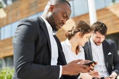 De Afrikaanse zakenman leest een sms-bericht royalty-vrije stock fotografie