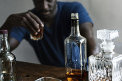 De Afrikaanse de zitting van de afdalingsmens het drinken slechte gewoonte van de whisky alcoholische verslaving stock afbeelding