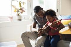 De Afrikaanse zoon van het vaderonderwijs hoe te om gitaar te spelen royalty-vrije stock foto's