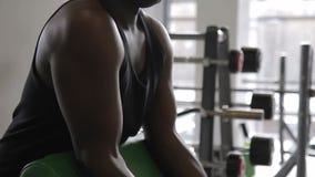 De Afro-Amerikaanse sportman doet de barbellvoorzijde opheft status dichtbij geneigde bank in de moderne gymnastiek stock videobeelden