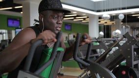 De Afro-Amerikaanse sportman zit op de groene bank in de gymnastiek en trekt de handvatten van exserciser uit stock footage