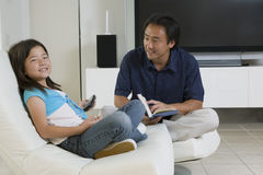 De Afstandsbediening en het Boek van vaderand daughter with thuis Stock Fotografie