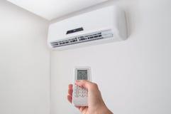 De afstandsbediening van de handholding voor airconditioner op witte muur Stock Foto's