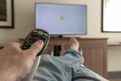 De afstandsbediening van de handholding voor TV terwijl het ontspannen met voeten propped omhoog - Ondiepe velddiepte royalty-vrije stock afbeelding