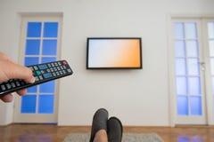 De afstandsbediening van holdingstv met een televisie als achtergrond Stock Foto's