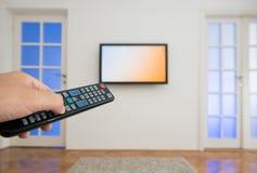 De afstandsbediening van holdingstv met een televisie als achtergrond Royalty-vrije Stock Foto