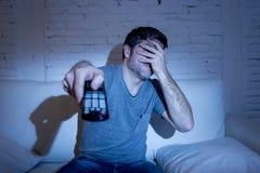 De afstandsbedieningzitting van TV van de mensenholding bij woonkamerlaag het letten op televisie die zijn ogen blokkeren Royalty-vrije Stock Foto