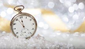 De aftelprocedure van de nieuwjarenvooravond Notulen aan middernacht op een oud horloge, bokeh feestelijk stock foto