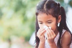 De afvegende en schoonmakende neus van het zieke Aziatische kindmeisje met weefsel royalty-vrije stock foto