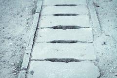 De afvoerkanaaldekking wordt gemaakt van oud, dilapidated cement met een barst en zou moeten worden verbeterd royalty-vrije stock fotografie