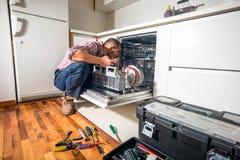 De afwasmachine van de manusje van allesreparatie in de keuken royalty-vrije stock fotografie