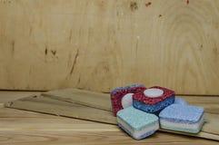 De afwasmachinecapsules op houten raad sluiten omhoog royalty-vrije stock fotografie