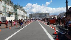De afwerkingslijn van de marathon van St. Petersburg Weergeven van de lopende atleten van de rug Steun van ventilators stock videobeelden