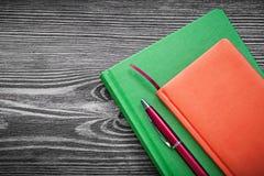 De agenda boekt pen op het uitstekende houten concept van het raadsbureau stock fotografie