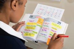 De Agenda van onderneemsterwriting schedule in stock fotografie