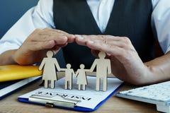 De agent beschermt familiecijfers Levensverzekeringspolis inzake een bureau stock afbeeldingen