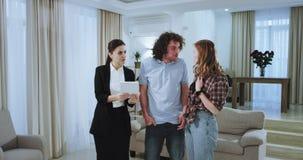 De agent die van het vrouwenhuis de nieuwe moderne flat tonen aan een charismatisch paar zij die een tablet gebruiken aan het ver stock video