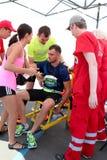 De agent krijgt medische aandacht Paramedicus die mannelijk agent wihh ongeval helpen Stock Foto's
