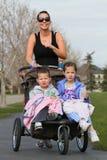 De agent van de vrouw met jonge geitjes in wandelwagen stock foto's