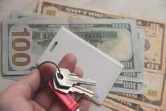 De agent van de onroerende goederenhuur, makelaar in onroerend goed houdt de sleutels aan de flat in dollars Het concept uitwisse stock foto's