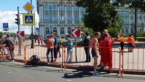 De agenten beëindigen de definitieve meters van de marathon van St. Petersburg Artsensteun één van de atleten die spierproblemen  stock footage