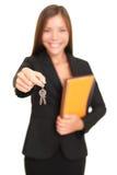 De agentenvrouw die van onroerende goederen sleutels geeft Stock Foto's