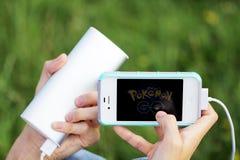 2 de agosto de 2016 - Minsk, Bielorrússia: Mãos com iphone e Pokemon Fotografia de Stock