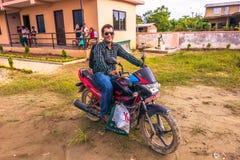 30 de agosto de 2014 - o motociclista nas crianças dirige em Sauraha, Nepal Imagem de Stock Royalty Free