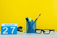 27 de agosto Imagem do 27 de agosto, calendário no fundo amarelo com materiais de escritório Adultos novos fotografia de stock royalty free