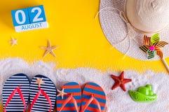 2 de agosto Imagen del calendario del 2 de agosto con los accesorios de la playa del verano y el equipo del viajero en fondo Árbo Imagen de archivo
