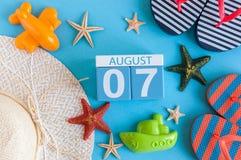 7 de agosto Imagen del calendario del 7 de agosto con los accesorios de la playa del verano y el equipo del viajero en fondo Árbo Fotos de archivo