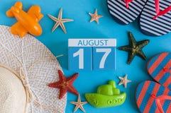 17 de agosto Imagen del calendario del 17 de agosto con los accesorios de la playa del verano y el equipo del viajero en fondo Ár Imagen de archivo