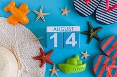 14 de agosto Imagen del calendario del 14 de agosto con los accesorios de la playa del verano y el equipo del viajero en fondo Ár Fotografía de archivo