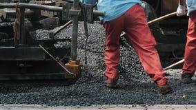 19 de agosto de 2018 Suzhou, China Trabajadores que hacen el asfalto con las palas en la construcción de carreteras metrajes