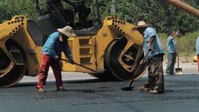 19 de agosto de 2018 Suzhou, China Trabajadores que hacen el asfalto con las palas en la construcción de carreteras almacen de metraje de vídeo