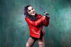 De agressieve punkvrouw slaat iemand met een knuppel, in rood leerjasje Royalty-vrije Stock Afbeeldingen