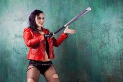 De agressieve punkvrouw slaat iemand met een knuppel, in rood leerjasje Royalty-vrije Stock Foto