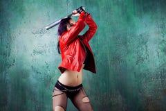 De agressieve punkvrouw slaat iemand met een knuppel, in rood leerjasje stock afbeeldingen