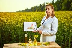 De de agronoomvrouw of landbouwer onderzoekt het tot bloei komende gebied van verkrachtingscanola gebruikend tablet met infograph royalty-vrije stock foto