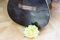 De akoestische gitaar die op bed lage hoek leggen schoot van bodem met plectrum op het lichaam stock foto's