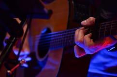De akoestische speeldetails van de gitaargitarist Muzikale instrumant met uitvoerdershanden royalty-vrije stock afbeeldingen