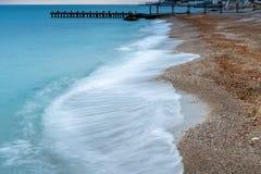 De aktuella havsvågrullarna på stranden, dyster höst arkivbild