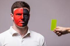 De Albanese voetbalventilator van het nationale team van Albanië krijgt gele kaart op grijze achtergrond Stock Fotografie