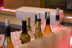 De alcohol drinkt flessen in ijs in staaf Stock Afbeelding