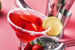 De alcoholische cocktail van aardbeimargarita met tequila, likeur, bessen, citroensap, suiker en ijs, de zomer roze achtergrond,  royalty-vrije stock fotografie