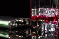 De alcoholische drankalcohol en ijs van de roestvrij staalfles op lijst met rode whisky stock afbeelding
